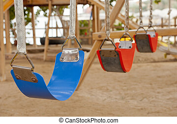 Swings in a childrens play area - Closeup of colorful...