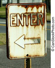 DIRECTIONAL SIGN - A rusty directional sign with the word...
