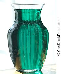GLASS VASE - A glass vase  filled with a colorful liquid