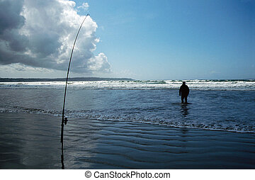 Fisherman and fishing rod on the beach - Fisherman and...