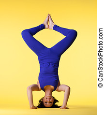 happy woman head stand blue on yellow - young happy woman in...