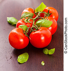 vine-ripened tomatoes with basil on a wooden plate