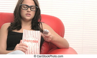 girl on an armchair watching tv - Young girl in glasses on...