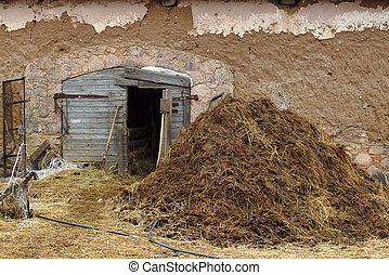 Manure pile near the old barn in the farm