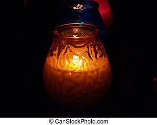 Candles in glass glow in the darkness to create romantic...