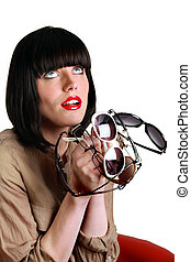 Woman holding several pairs of sunglasses