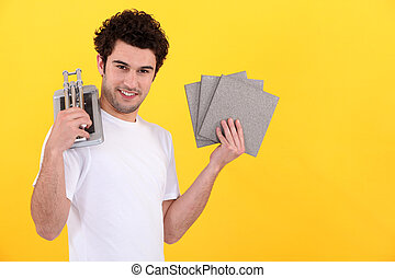 Young man with a tile cutter