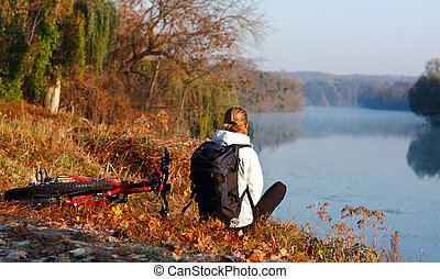 Woman cyclist enjoy the recreation on the river-side....