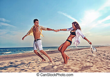 boy and girl running on beach - young boy and girl running...