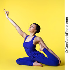 Woman doing yoga split in blue on yellow - young happy woman...