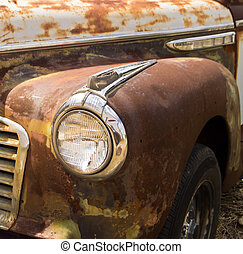 Closeup of vintage automobile with rust and headlight