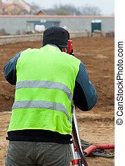 Building surveyor taking measurements on a construction site