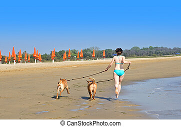 Girl with dogs running on the beach