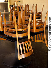 Closed Restaurant - Chairs and tables stacked in a closed...