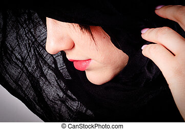 Part of a woman's face with black hood