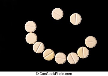 Smiling face made out of pills on black background