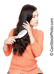 pretty woman combing her long black hair, isolated on white...