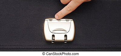closeup photo of a combination lock on a black suitcase with child hand