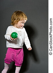 Cute little baby playing with green toy ball