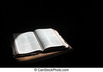 Open bible lying on a table - Old open bible lying on a...