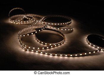 white led strip with a glue layer, background in the dark,...