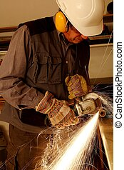 Worker with angle grinder an helmet and protectors