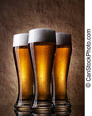 Three Beer into glass on a old stone - Three cold Beer into...