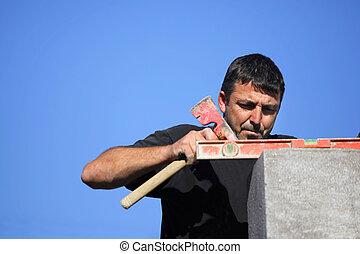 Tradesman using an axe and a bubble level