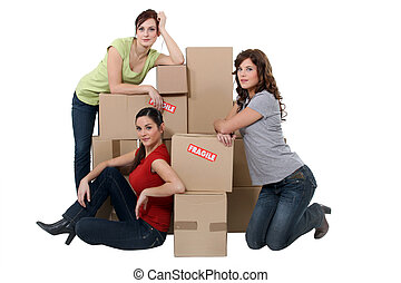Young women posing with their belongings on moving day