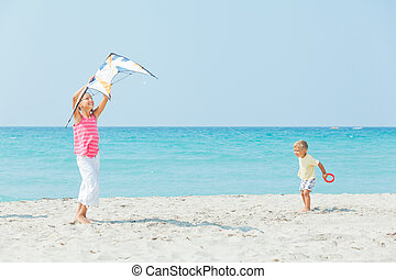 girl with brother on beach playing with a kite - Young cute...