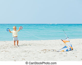 Cute boy on beach playing with a colorful kite - Little cute...