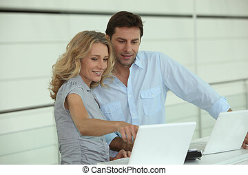 Couple at work on laptops