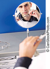 Face of a man in a mirror while he testing eyeglasses