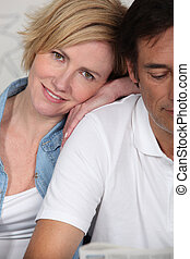 Couple lying dressed on their bed