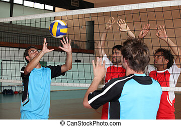 Young men playing volleyball