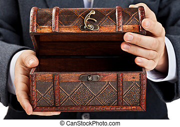 Hand holding treasure chest - Business man hand holding old...