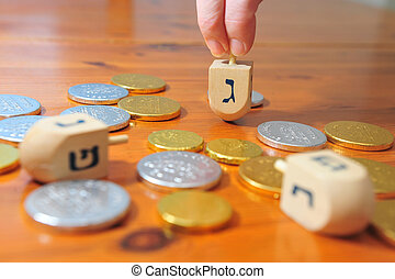 Hanukkah - Dreidels and Gelt - Photo of someone spinning a...