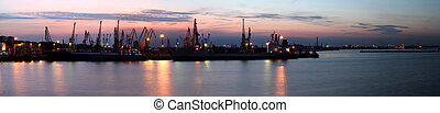 Silhouette of several cranes in a harbor, shot during...
