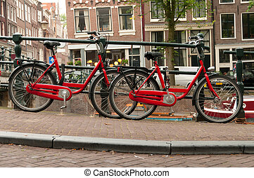Bikes on Amsterdam street - Red bikes parked on a street in...