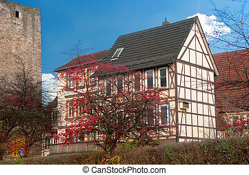 Half timbered house near old castle wall - Traditional...