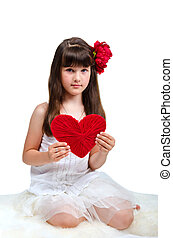 Adorable brunette girl wearing white dress holding red heart in her hands, isolated