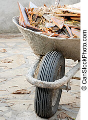 Wheelbarrow with waste - old used wheelbarrow details with...