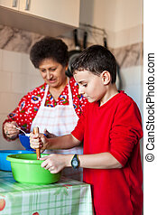 Grandson and grandmother making cookies - Kid helping his...