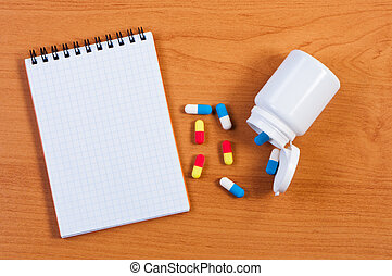Notebpad and pills on table top view.