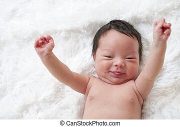 Newborn baby - Happy newborn baby with arms up in the air.