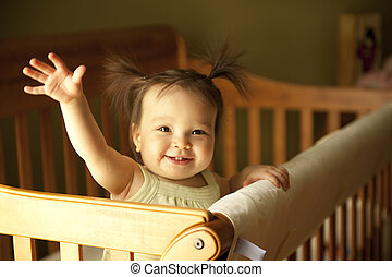 Baby standing up in crib - Baby girl waving hand and...