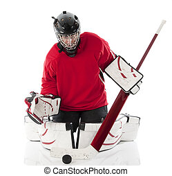 Ice hockey goalie blocking a puck in butterfly style. Photo...