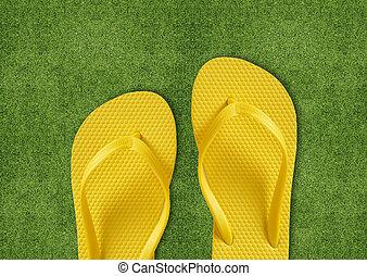 Yellow Flip Flops on green grass, summertime