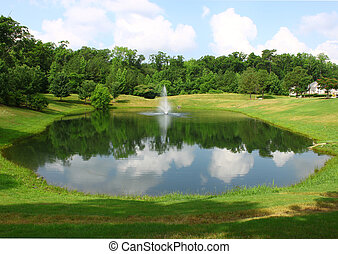 A manmade well manicured and landscaped pond and fountain on a gogeous summer day with room for your text.