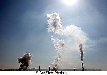 smokestack - Industrial smokestack with smoke clouds over...